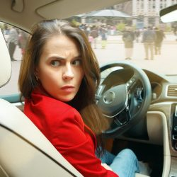Driving and stress. Young attractive woman driving a car. Screaming surprised caucasian model in elegant stylish red jacket sitting at modern vehicle interior. Businesswoman concept. Human emotions concepts