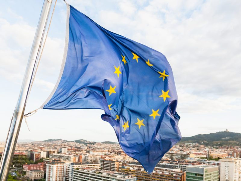 european union flag fluttering by wind above Barcelona city